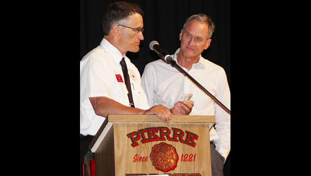 President Charlie Kludt presented Governor Daugaard with a 2015 Pierre Fire School Challenge coin.